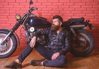 Man with beard, biker in leather jacket near motor bike in garage, brick wall background. Hipster, brutal biker on pensive face in leather jacket sit on floor near motorcycle. Brutal biker concept