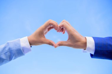 Hand heart gesture forms shape using fingers. Male hands in heart shape gesture symbol of love and romance. Love symbol concept. Hands put together in heart shape blue sky background