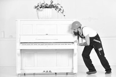 Handsome bearded strong man moving piano with open keyboard and glass vase with flowers on white background. Home service concept