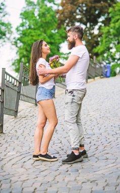 Guy prepared surprise bouquet for girlfriend. Romantic date walk. Gentlemans manners. Man gives flower bouquet to girl romantic date. Couple meeting for date park background. Bouquet always good idea
