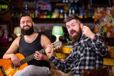 Man play guitar in pub. Live music concert. Acoustic performance in pub. Hipster brutal bearded with friend in pub. Cheerful friends sing song guitar music. Relaxation in pub. Friends relaxing in pu