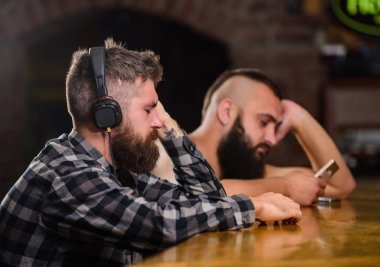 Friday relaxation in bar. Hipster bearded man spend leisure at bar counter. Order drinks at bar counter. Men with headphones and smartphone relaxing at bar. Avoid communication. Escape reality