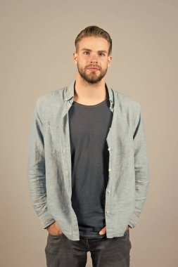 Man bearded strict face wears casual clothes, grey background. Man with beard unshaven guy looks handsome and well groomed casual clothes. Guy bearded attractive with hairstyle. Masculinity concept