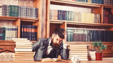 Difficult subject, confusing question, study, education, hard work, intellectual research concept. Man sits at table with many books. Mature man has serious face and thinks. Guy reads in library