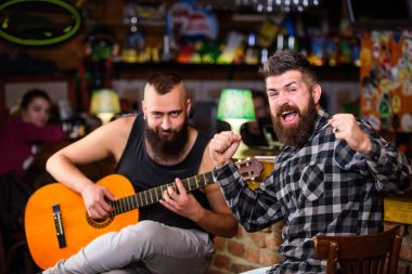 Cheerful friends sing song guitar music. Relaxation in pub. Friends relaxing in pub. Live music concert. Man play guitar in pub. Acoustic performance in pub. Hipster brutal bearded with friend in pub