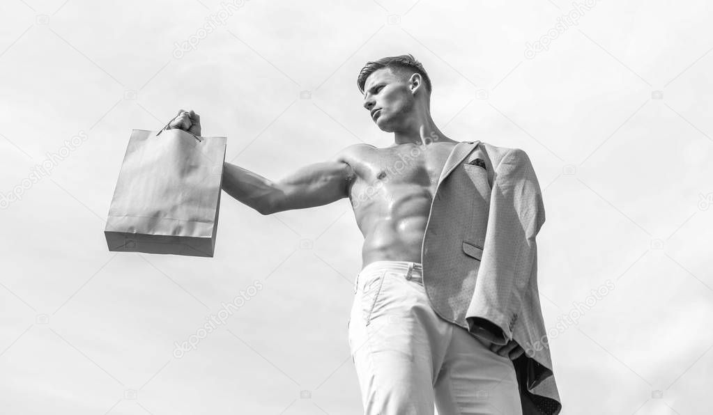 Guy attractive macho carry shopping bag made out of brown paper. Sales season. Man muscular athlete hold shopping bag sky background. Hot sales and discount. Take this package. Eco healthy products