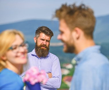 Couple in love dating while jealous husband fixedly watching on background. Lovers meeting outdoor flirt romance relations. Couple romantic date lover present bouquet flowers. Unrequited love concept