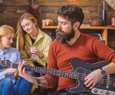 Man with hipster beard playing guitar at college party. Musician rehearsing new song. Bearded man entertaining two blond girls. Guitarist tuning his instrument. Man with calm face composing melody