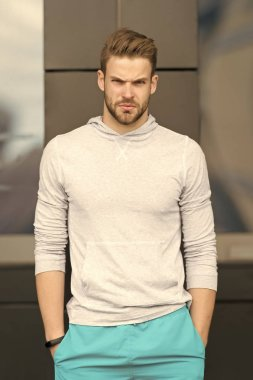 Sport fashion concept. Guy bearded and attractive cares about appearance. Man with bristle on serious face in sporty wear, urban background. Man with beard or unshaven guy in stylish sport clothes