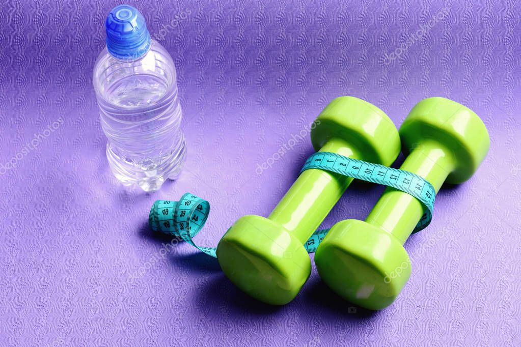 Dumbbells and measure tape in cyan color on purple background
