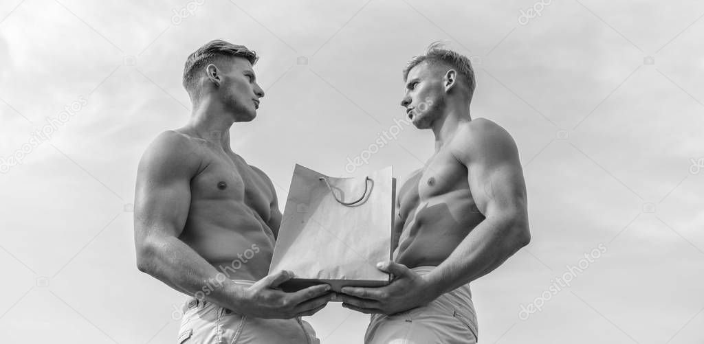 Guys attractive twins carry shopping bag made out of brown paper. Sales season. Men muscular athletes hold shopping bag sky background. Hot sales and discount. Brothers buy eco healthy products