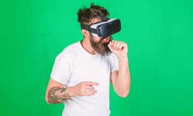 Man with beard in VR glasses, green background. Guy with VR glasses singing with imaginary microphone. Hipster on busy face use modern technologies for entertainment or education. VR musician concept