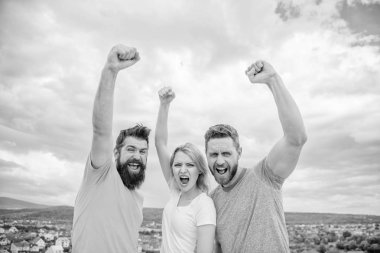 Ways to build ohesive team. Woman and men look confident successful sky background. Threesome stand happy confidently with raised fists. Behaviors of cohesive team. Celebrate success. Yes we can