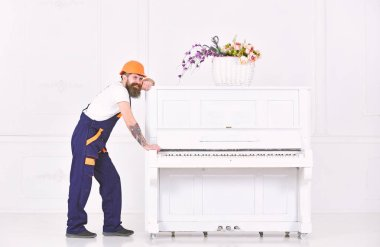 Strong worker having a break isolated on white background. Smiling guy with mustache trying to move white piano. Long day at work