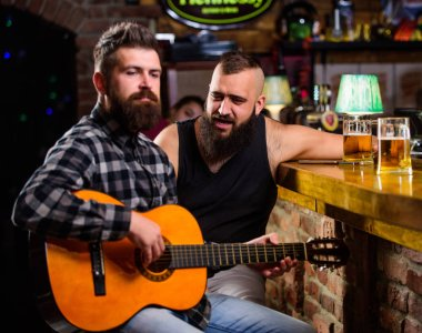 Friday relaxation in bar. Friends relaxing in bar or pub. Real men leisure. Hipster brutal bearded spend leisure with friend in bar. Man play guitar in bar. Cheerful friends relax with guitar music