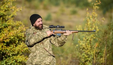 Hunter hold rifle. Bearded hunter spend leisure hunting. Focus and concentration of experienced hunter. Hunting masculine hobby concept. Man brutal gamekeeper nature background. Regulation of hunting