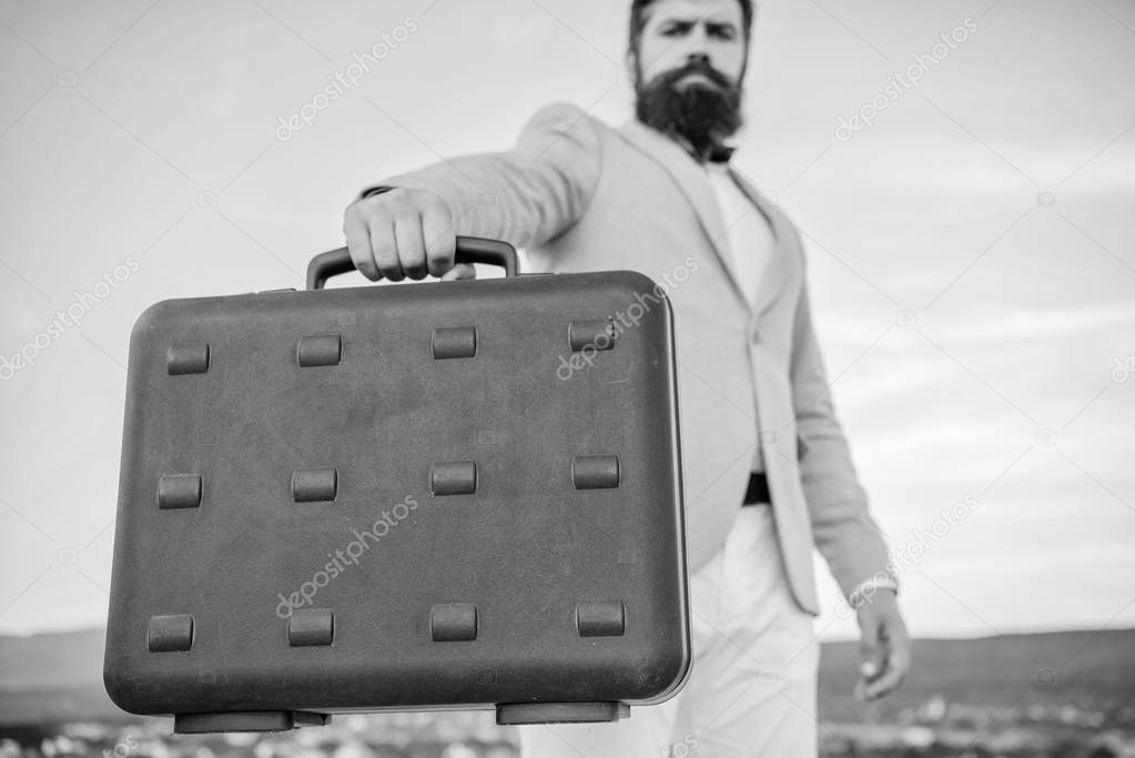 Business man formal suit carries briefcase sky background. Businessman presenting business case. Entrepreneur offer bribe. Illegal deal business. Hipster bearded face hold briefcase with bribe
