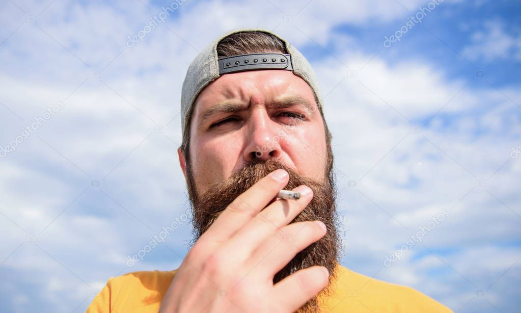 Take it easy. Smoking habit concept. Hipster thoughtful concentrated face with smoke flying out of mouth. Smoking outdoors. Man beard and mustache smoking sky background. Relaxing effect of smoking