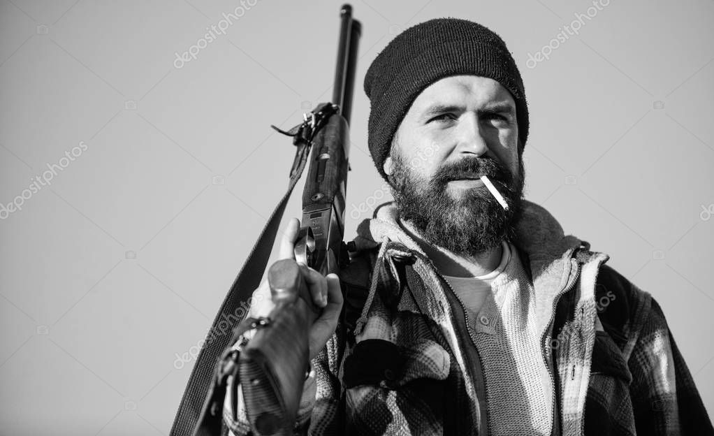 Man brutal bearded guy gamekeeper blue sky background. Brutality and masculinity. Hunter with rifle gun close up. Guy bearded hunter spend leisure hunting and smoking. Hunting masculine hobby concept