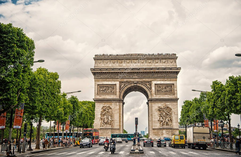 Paris, France - June 02, 2017: Arch monument in centre of busy avenue. Arc de Triomphe on cloudy sky. Vacation and sightseeing in french capital. Victory liberation and honour concept