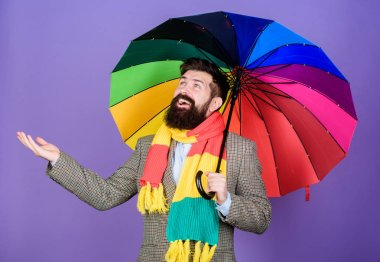 An umbrella is needed on a rainy day. Autistic or rain man holding colorful umbrella. Autism. Bearded man checking if it rains. Fashion man with colorful accessories. Let it rain