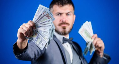 A profitable business. Bearded man holding cash money. Making money with his own business. Currency broker with bundle of money. Rich businessman with us dollars banknotes. Business startup loan