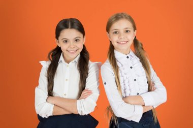 Keeping arms crossed. School children with a fashion forward look. Cute schoolgirls. Little girls wearing school uniform. Stylish girls in pigtails dressed for school. Back to school fashion style