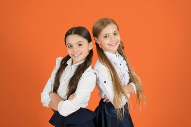 In traditional black and white. Little girls wearing school uniform. School children with a fashion forward look. Cute schoolgirls. Small girls in pigtails dressed for school. Back to school fashion