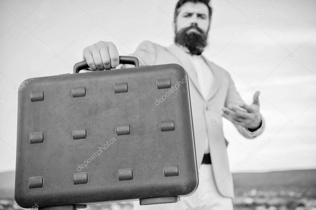 Entrepreneur offer bribe. Illegal deal business. Hipster bearded face hold briefcase with bribe. Business man formal suit carries briefcase sky background. Businessman presenting business case