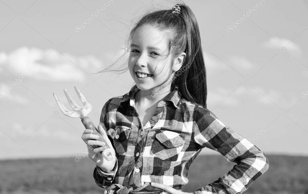 Kid cheerful gardener hold rake blue sky background. Girl gardener with hand rake. Gardening and harvesting concept. Gardening activity. Little girl gardener at family farm. Childhood in countryside