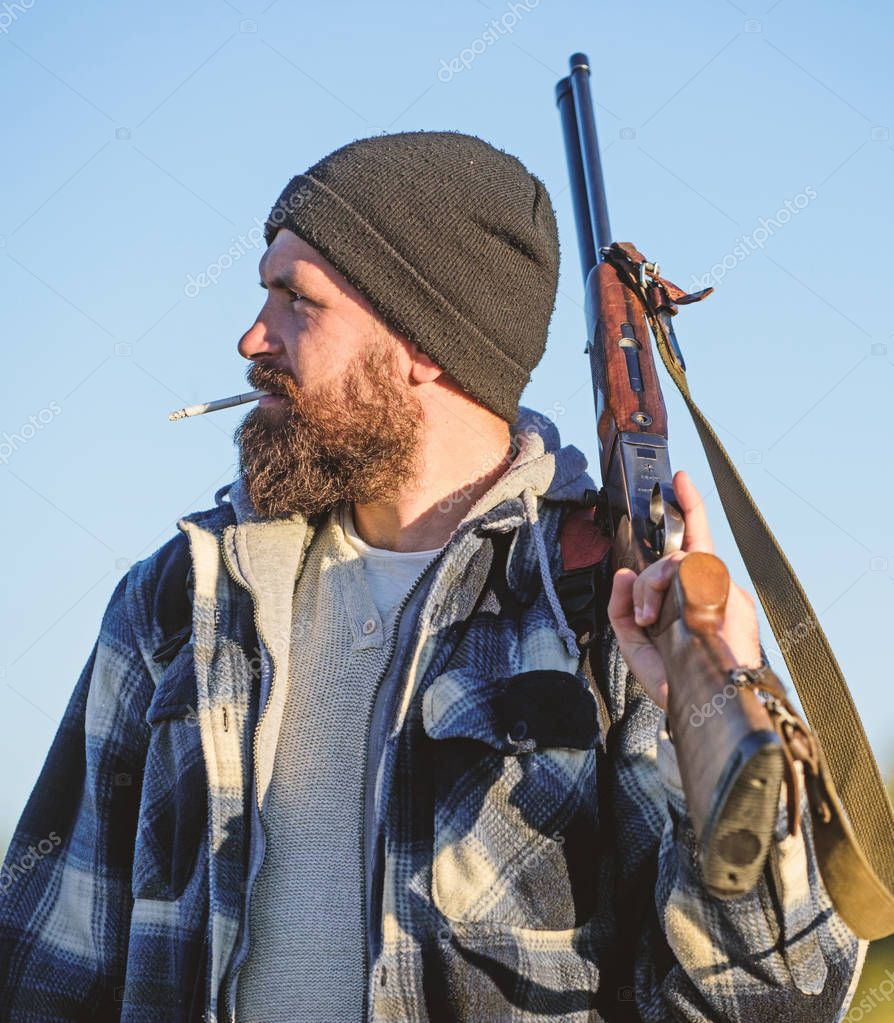 Hunting masculine hobby concept. Man brutal bearded guy gamekeeper blue sky background. Hunter with rifle gun close up. Guy bearded hunter spend leisure hunting and smoking. Brutality and masculinity