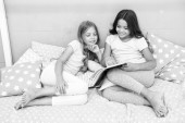 Fotografie Children read book in bed. Girls best friends read fairy tale before sleep. Best books for kids. Reading before bed can help sleep better at night. Stories every kid should read. Family tradition