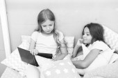 Fotografie Children read book in bed. Stories every kid should read. Family tradition. Girls best friends read fairy tale before sleep. Best books for kids. Reading before bed can help sleep better at night
