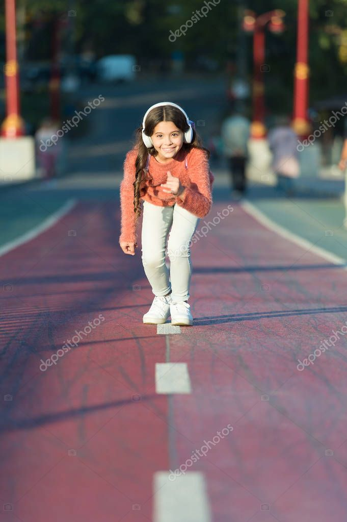 Ready to run. Little girl standing on start line while running outdoor. little girl listen music. Mp3 player. happy little girl. Audio book. Kid in headphones. out for a run. Enjoying a morning run