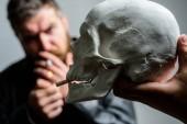 Muž si kouření cigaret lidská lebka symbol smrti. Škodlivé návyky. Poškodit zdraví kouření a smrt. Zničte své zdraví. Kouření je škodlivé. Zvyk kouřit tabák přinést poškození vašeho těla