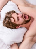Get adequate and consistent amount of sleep every night. Expert tips on sleeping better. How much sleep you actually need. Bearded man sleeping face relaxing on pillow. Man handsome guy lay in bed