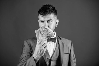 Man formal suit hold pile of dollar banknotes blue background. Businessman got cash money. Richness and wellbeing concept. Get cash money easy and quickly. Smell of money. Easy cash loans