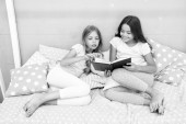Fotografie Children read book in bed. Family tradition. Girls best friends read fairy tale before sleep. Best books for kids. Reading before bed can help sleep better at night. Stories every kid should read