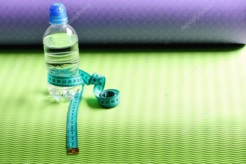 Water bottle and flexible ruler in blue on yoga mat