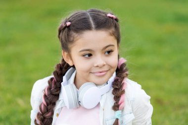 happy little girl. little girl listen music. Kid in headset. Stylish child relax on green grass. Spring mood. Mp3 player. time to relax. girl with mp3. listen mp3. Finding a peaceful place to relax