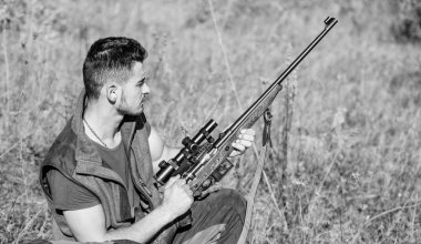 Hunting hobby and leisure. Man charging hunting rifle. Hunting equipment concept. Hunter with rifle looking for animal. Hunter khaki clothes ready to hunt nature background. Hunting shooting trophy
