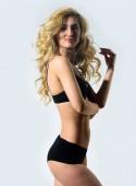 Intimhygiene. Sexy Frau mit langen lockigen Haaren. Haare Schönheit des sinnlichen Mädchen. Perfekte Körperform. Sexy blonde Frau. Erotische Dessous und Unterwäsche. Mode-Modell mit Fit Bauch. Selbstuntersuchung