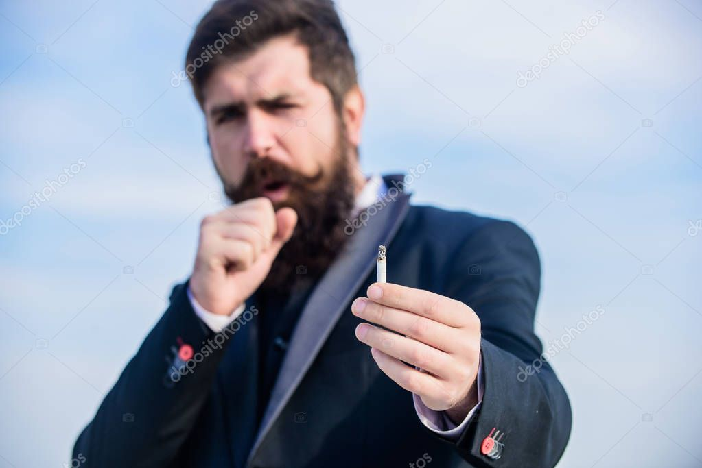 Guy cigarette enjoy nicotine influence. Man with beard mustache hold cigarette. Cigarettes help us with everything from boredom to anger management. Bearded hipster smoking cigarette sky background
