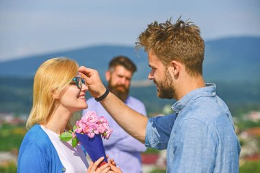 Couple in love dating while jealous husband fixedly watching on background. Unrequited love concept. Lovers meeting outdoor flirt romance relations. Couple romantic date lover present bouquet flowers