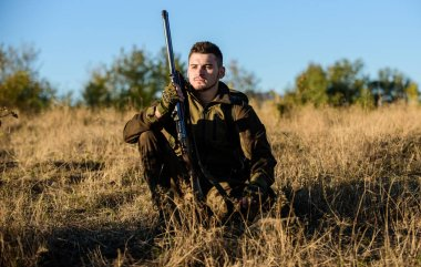 Rest for real man concept. Hunter with rifle relaxing in nature environment. Tired but satisfied. End of season. Hunter enjoy nature view. Hunting hobby leisure. Hunter satisfied with catch relaxing