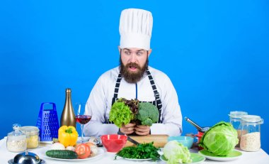Vegetarian. Mature chef with beard. Healthy food cooking. Chef man in hat. Secret taste recipe. Dieting and organic food, vitamin. Bearded man cook in kitchen, culinary. Impossible choice