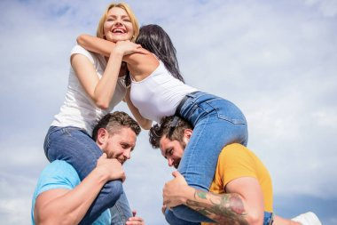 Couples in love having fun. Men carry girlfriends on shoulders. Summer vacation and fun. Couples on double date. Inviting another couple to join. Friendship of families. Twice fun on double date