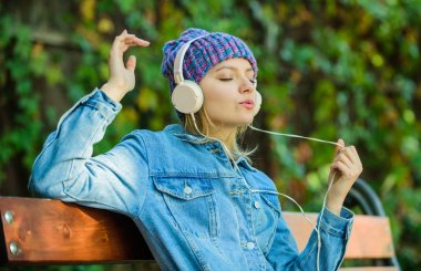 modern technology instead of reading. relax in park. hipster girl with mp3 player. hipster woman in headset. audio book or mp3 player. style and music. listening music in park on mp3. listen to mp3