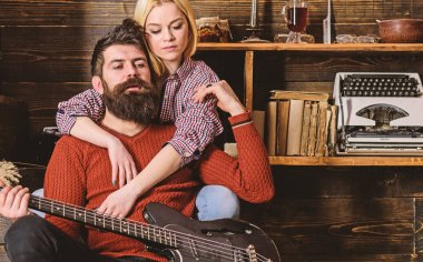 Lady and man with beard on dreamy faces hugs and plays guitar. Couple in wooden vintage interior enjoy guitar music. Couple in love spend romantic evening in warm atmosphere. Romantic evening concept