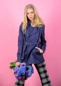 Fotografie Kleidung und Accessoires. Modelmädchen tragen Mantel für Frühling und Herbst. Trenchcoat-Trend. muss Konzept haben. modischer Mantel. Frau mit blonden Haaren posiert Mantel mit Blumenstrauß